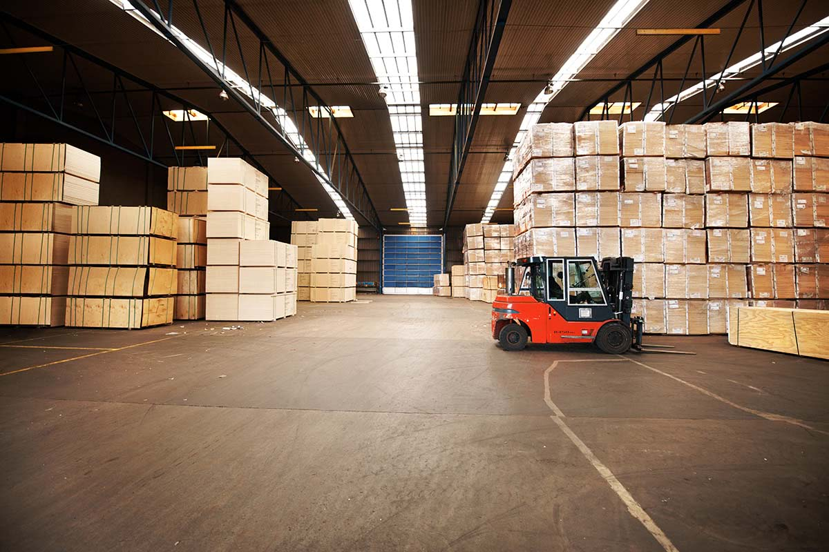 A large warehouse storing big boxes with a forklift.